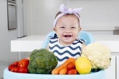 Aanbiddelijk babymeisje met groenten op stoel Royalty-vrije Stock Foto's