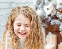 Aanbiddelijk blond meisje die met gesloten ogen, Kerstmis lachen stock fotografie