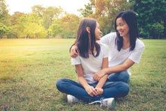 Aanbiddelijk Concept: Vrouw en kind die en het glimlachen geluk in het park koesteren voelen royalty-vrije stock afbeelding
