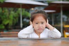 Aanbiddelijk drukte weinig Aziatisch kindmeisje teleurstelling of ongenoegen op de houten lijst met het kijken uit camera stock fotografie