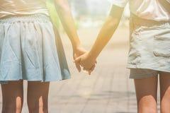 Aanbiddelijk Familieconcept: Twee zusters die op gang bij openbaar park lopen en hand samen houden royalty-vrije stock afbeeldingen