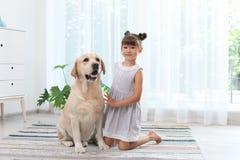 Aanbiddelijk geel labrador retriever en meisje stock afbeeldingen