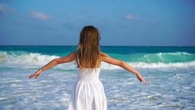 Aanbiddelijk gelukkig meisje die op wit strand op de oceaan kijken Lawaaierige overzees en een klein leuk jong geitje stock video