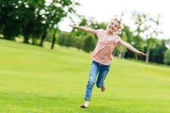 aanbiddelijk gelukkig meisje met open wapens die op groen gras lopen stock afbeeldingen