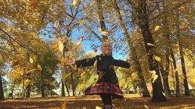 Aanbiddelijk gelukkig schoolmeisje die de gevallen bladeren werpen die omhoog, in het de herfst bos Mooie meisje binnen spelen di stock footage