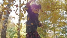 Aanbiddelijk gelukkig schoolmeisje die de gevallen bladeren werpen die omhoog, in het de herfst bos Mooie meisje binnen spelen di stock videobeelden