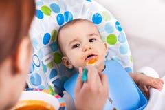 Aanbiddelijk geniet van weinig babyjongen etend fruitbrij royalty-vrije stock afbeelding