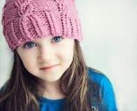 Aanbiddelijk glimlachend kindmeisje in roze gebreide hoed royalty-vrije stock foto's