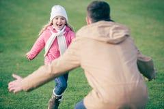 Aanbiddelijk glimlachend meisje die aan vader lopen stock foto's