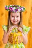 Aanbiddelijk glimlachend meisje met lang blond haar die bloemen hoofdkroon dragen en rieten mand met gele eieren houden Royalty-vrije Stock Foto