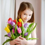 Aanbiddelijk glimlachend meisje met tulpen Stock Foto's