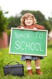 Aanbiddelijk glimlachend peutermeisje met terug naar het bord van de schooltekst Royalty-vrije Stock Afbeeldingen