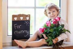 Aanbiddelijk glimlachend weinig jongen met bloeiende roze rozen in bos Stock Afbeelding
