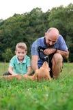 Aanbiddelijk glimlachend weinig jongen met zijn hipstervader, die met huisdierenhond spelen Royalty-vrije Stock Afbeeldingen
