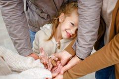 Aanbiddelijk glimlacht weinig krullend blonde in beige gebreide sweater sluw royalty-vrije stock afbeeldingen