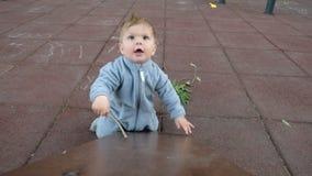 Aanbiddelijk grappig babyspel bij speelplaats onder zorg van zijn hipsterouders stock footage