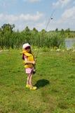 Aanbiddelijk houdt weinig blond Kaukasisch meisje hengel Zij draagt in reddingsvest zonnebril, en hoed Zij is bereid te vissen Royalty-vrije Stock Afbeeldingen