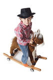 Aanbiddelijk jong geitje dat een stuk speelgoed paard berijdt Stock Foto's