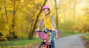 Aanbiddelijk jong meisje die een fiets in een stadspark berijden op zonnige de herfstdag Actieve familievrije tijd met jonge geit royalty-vrije stock fotografie
