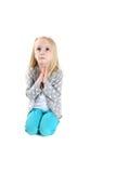 Aanbiddelijk jong meisje die in gebed knielen die omhoog eruit zien stock foto