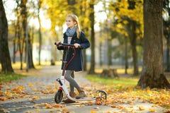 Aanbiddelijk jong meisje die haar autoped in een stadspark berijden op zonnige de herfstavond Preteen vrij kind die een rol berij stock foto's