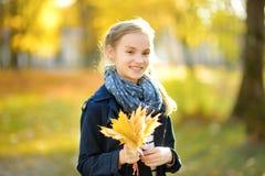 Aanbiddelijk jong meisje die pret op mooie de herfstdag hebben Het gelukkige kind spelen in de herfstpark Jong geitje die geel da stock foto's