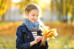 Aanbiddelijk jong meisje die pret op mooie de herfstdag hebben Het gelukkige kind spelen in de herfstpark Jong geitje die geel da royalty-vrije stock foto's