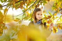 Aanbiddelijk jong meisje die pret op mooie de herfstdag hebben Het gelukkige kind spelen in de herfstpark Jong geitje die geel da stock afbeeldingen