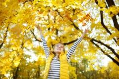 Aanbiddelijk jong meisje die pret op mooie de herfstdag hebben Het gelukkige kind spelen in de herfstpark Jong geitje die geel da royalty-vrije stock foto