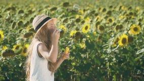 Aanbiddelijk kind in de bel van hoedenslagen bij zonnebloemengebied stock videobeelden