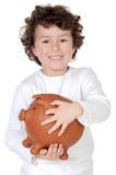 Aanbiddelijk kind met zijn besparingen in zijn spaarpot van piggy Stock Afbeeldingen