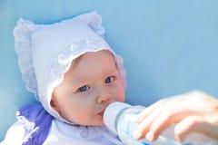 Aanbiddelijk kindmeisje met zuigelingsformule in flessenconsumptiemelk royalty-vrije stock fotografie
