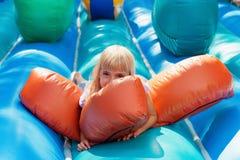 Aanbiddelijk klein meisje die op een opblaasbaar ontploffingstuk speelgoed liggen voor jong geitje Royalty-vrije Stock Foto