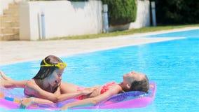 Aanbiddelijk klein zustersspel in openlucht zwembad stock footage