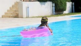 Aanbiddelijk klein zustersspel in openlucht zwembad stock videobeelden