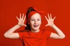Aanbiddelijk kleutermeisje dat palmen en grappig grimas toont Leuk blij Spaans kind die pret hebben Pretconcept stock foto