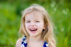 Aanbiddelijk lachend meisje met lang blond krullend haar, stock afbeeldingen