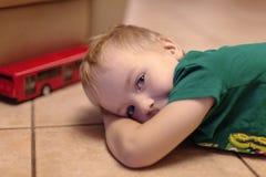 Aanbiddelijk legt weinig jongen met blauwe ogen op de ceramische vloer met stuk speelgoed rode bus Blondehaar, groene t-shirt royalty-vrije stock foto