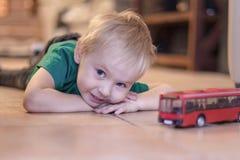 Aanbiddelijk legt weinig jongen met blauwe ogen op de ceramische vloer met stuk speelgoed rode bus Blondehaar, groene t-shirt royalty-vrije stock fotografie