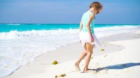 Aanbiddelijk meisje bij strand die heel wat pret hebben Sportief actief jong geitje die op seahore dansen stock videobeelden