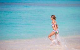 Aanbiddelijk meisje bij strand die heel wat pret in ondiep water hebben royalty-vrije stock afbeeldingen