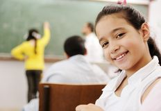 Aanbiddelijk meisje dat in school glimlacht Stock Fotografie