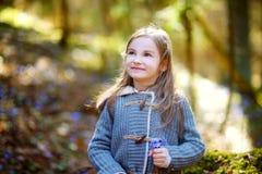 Aanbiddelijk meisje die de eerste bloemen van de lente in het hout plukken Stock Foto's