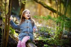 Aanbiddelijk meisje die de eerste bloemen van de lente in het hout plukken Stock Afbeelding