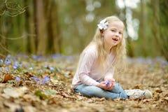 Aanbiddelijk meisje die de eerste bloemen van de lente in het hout op mooie zonnige de lentedag plukken stock afbeeldingen