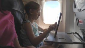 Aanbiddelijk meisje die door een vliegtuig reizen en een digitale tablet gebruiken tijdens de vlucht Concept die in het buitenlan stock videobeelden