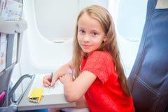 Aanbiddelijk meisje die door een vliegtuig reizen Het beeld van de jong geitjetekening met kleurrijke potloden die dichtbij vlieg stock fotografie