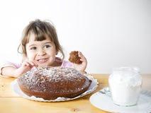 Aanbiddelijk meisje die een eigengemaakte chocoladecake eten Stock Foto