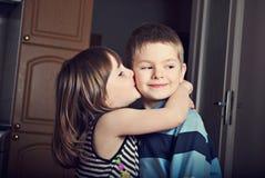 Aanbiddelijk meisje die een jongen kussen Stock Afbeeldingen