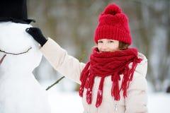 Aanbiddelijk meisje die een sneeuwman in mooi de winterpark bouwen Het leuke kind spelen in een sneeuw royalty-vrije stock foto